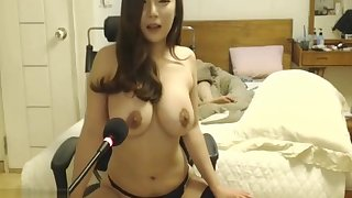 Korean beauty in stockings plays with her hefty tits